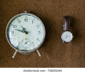 Vintage table clock and man's wristwatch on a brown background. Artwork