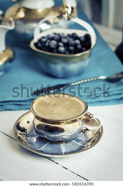 Vintage Table service on a white table, with a cup of black espresso, vintage toning