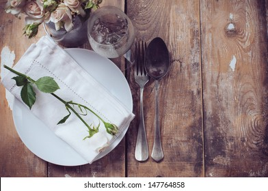 Vintage table setting with roses, antique rustic dishes and cutlery on the wooden background, close-up