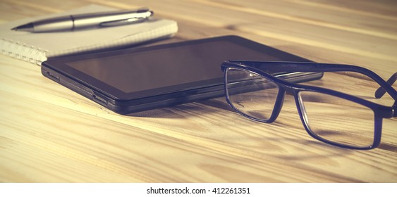 Vintage. Tablet PC, notebook or open a folder and glasses in the office desk.