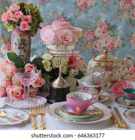 Vintage tea party - tea cups, teapots and gold cutlery flatware with vintage silver trophy full of roses