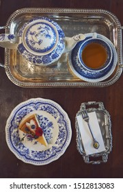 Vintage tea service on the wooden table with cup of tea and rustick style cheesecake