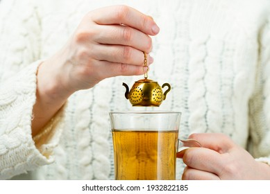 Vintage tea strainer. Woman brews tea with gold tea strainer in the shape of a teapot.
