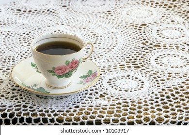 Vintage teacup and saucer on a beautiful crochet tablecloth.