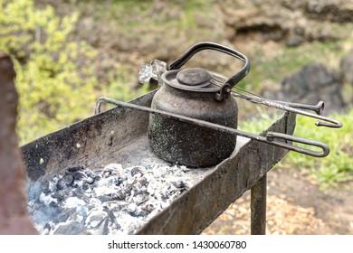Vintage teakettle on open fire.
