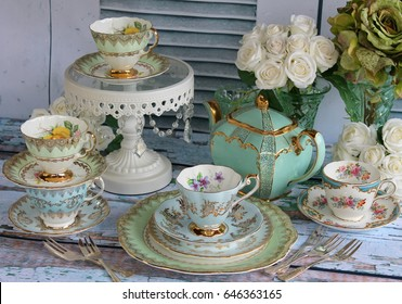Vintage teapot, tea cups and cake stand on a distressed wood table - afternoon tea party