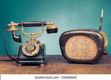 Vintage telephone, old retro radio on wood table