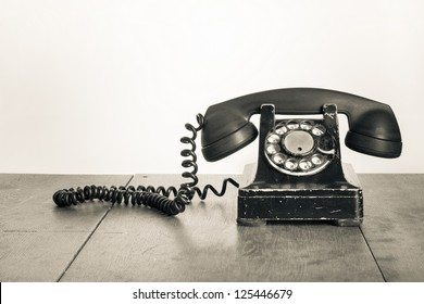 Vintage telephone on old table sepia photo