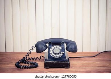 Vintage telephone on old table near wood wall