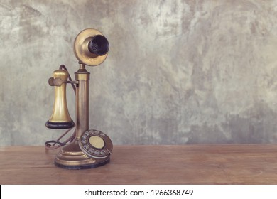 Vintage telephone on wooden table with cement wall background, image with copy space.