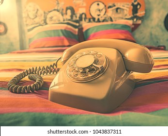 Vintage telephone over the bed of a colorful retro bedroom.Toned image with instagram filter and sun flare rays