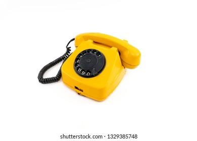 Vintage telephone. Yellow old phone isolated on white background.