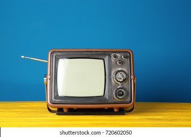 Vintage television on wooden table near color wall