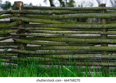Vintage texture of an old wicker fence on green grass. Traditional rural decorative fence.