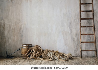 Vintage textured cement wall with old scratched wooden floor, metal anchor, retro barrel, ladder and pile of rope. Fishing or boat accessories. Interior photo in neutral tones