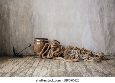 Vintage textured cement wall with old scratched wooden floor, metal anchor, retro barrel and pile of rope. Fishing or boat accessories. Interior photo in neutral tones