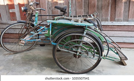 Vintage Thai style tricycle with wooden wall background. Urban decor object.