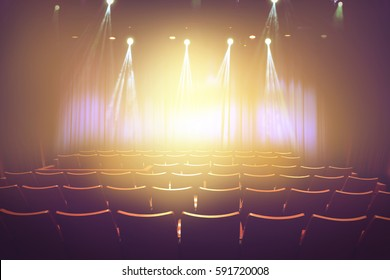 vintage theater with lighting spot on stage before showtime , empty auditorium with seats