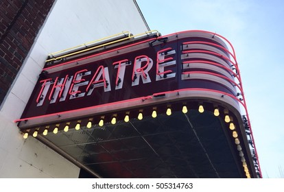 "Vintage theatre marquee with the word ""theatre"" in neon lights."
