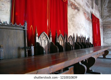 Vintage throne room interior with old wooden seats and long wooden table, Hunedoara, Romania