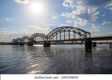 Vintage through (tied) arch railway bridge (Dzelzcela tilts) over Daugava river in Riga, Latvia on a sunny day with clouds in a blue sky.