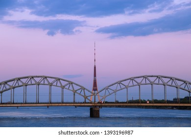 Vintage through (tied) arch railway bridge (Dzelzcela tilts) over Daugava river and the radio and TV tower (televizijas tornis) in Riga, Latvia at dawn, after sunset, with blue clouds in a pink sky.