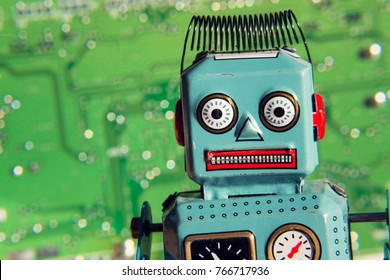 Vintage tin toy robot with green computer circuit board background, artificial intelligence concept
