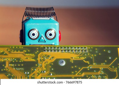 Vintage tin toy robot hiding behind orange computer circuit board, artificial intelligence concept