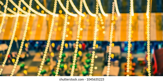 vintage tone abstract blur image of night festival in city with bokeh of light bulb.