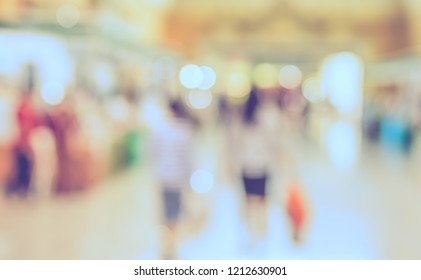 Vintage tone Abstract blur image of People walking at shopping mall or exhibition hall with bokeh for background usage .