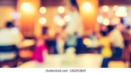 Vintage tone abstract blur image of  People at Restaurant or Cafe with bokeh for background usage .