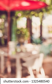 Vintage tone abstract blur image of  Outdoor restaurant or cafe with green bokeh for background usage .