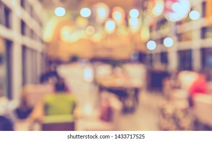 Vintage tone abstract blur image of Cafe or Restaurant  on night time with bokeh for background usage .