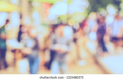 Vintage tone Abstract Blurred image of People walking at Local day market in garden with bokeh for background usage .