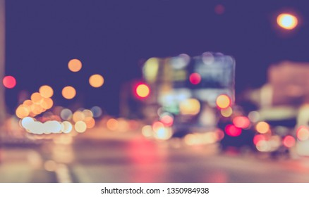 Vintage tone abstract blurred image of Road in night time with light bokeh  for background usage.