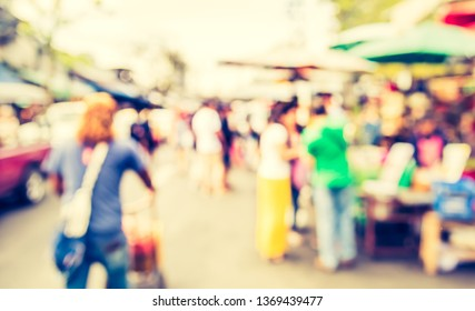 Vintage tone Abstract Blurred image of People walking at Street day market with bokeh for background usage .