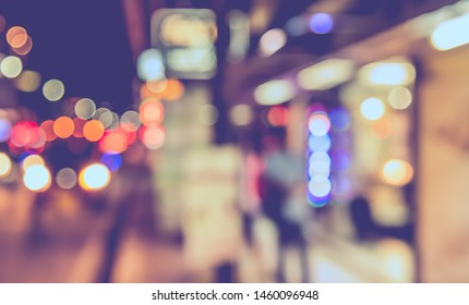 Vintage tone abstract blurred image of People walking at footpath in night time with light bokeh  for background usage.