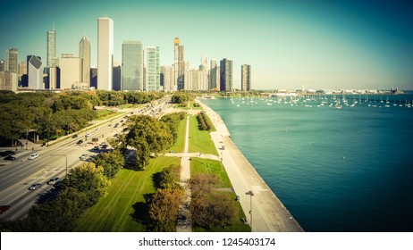 Vintage tone aerial view of downtown Chicago tall skylines from Grant Park. Tranquil Michigan Lake and green trees along Lake Shore Drive. Row of docked boats and yachts on the background