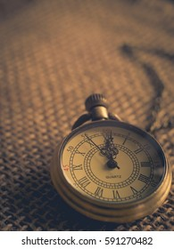 Vintage tone antique pocket watch on wooden background wallpaper in old and retro style with copy space