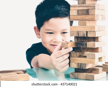 Vintage tone of asian kid is playing wood blocks tower game for practicing physical and mental skill. Photo is focused is hands.