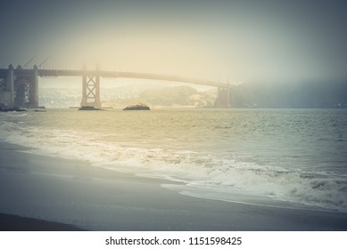 Vintage tone beautiful view Golden Gate from Baker beach in foggy summer day. Strong waving sea, nature background, San Francisco, California, USA