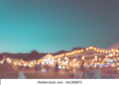 vintage tone blur image of festival is celebrated at night with bokeh from the lights that are decorated throughout the event for background
