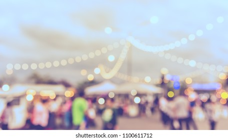 Vintage tone blur image of Food truck at  street night festival with bokeh for background usage .
