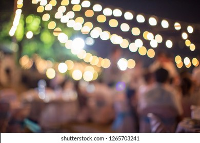 vintage tone blur image of food stall at night festival with bokeh for background usage. Festival Event Party with People Blurred Background. Blur people having sunset beach party in summer vacation