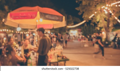vintage tone blur image of food stall at night festival with bokeh for background usage .