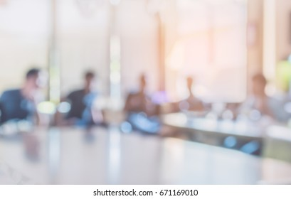 vintage tone blur image of group of people in meeting room for background.