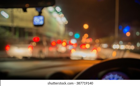 vintage tone blur image of inside cars with bokeh lights from traffic jam on night time for background.
