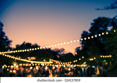 vintage tone blur image of night festival in garden with bokeh for background usage .