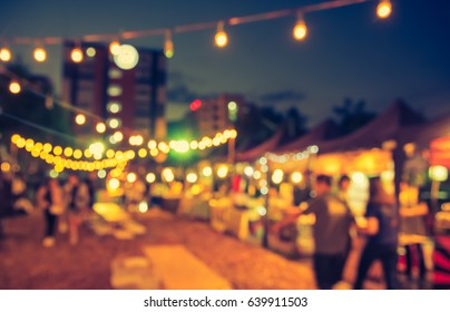vintage tone blur image of night festival on street with bokeh for background usage .