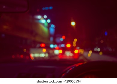 vintage tone blur image of people driving car on night time for background usage.(take photo from inside)